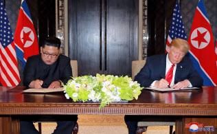 米朝首脳会談後、共同声明に署名する金正恩委員長(左)とトランプ大統領(6月12日、シンガポール)=ロイター