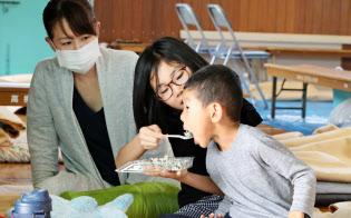地震発生から一夜明け、避難所で配られた朝食をとる子どもたち(19日午前、大阪府高槻市)