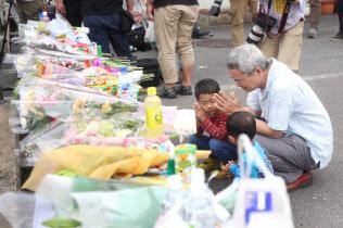 塀の下敷きになり小学生が亡くなった現場付近の献花台で手を合わせる人(19日午前、大阪府高槻市)