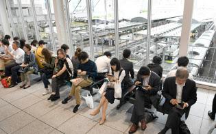 地震で交通機関の運行が止まり、再開を待つ人たち(18日、JR大阪駅)