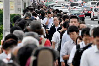 交通機関の運転見合わせが続き、徒歩で目的地に向かう人たち(18日、大阪市)
