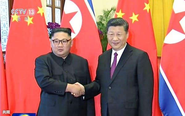中国中央テレビが19日放映した、北京で握手する北朝鮮の金正恩朝鮮労働党委員長(左)と中国の習近平国家主席の映像=共同