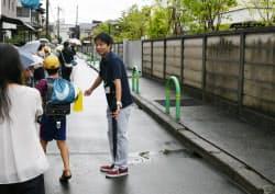 塀を避けて登校するよう児童を誘導する小学校の教員(20日午前、大阪府茨木市)