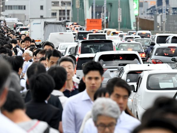 鉄道の運休に加え道路の大渋滞で、徒歩で帰る人たちが歩道を埋めた(18日、大阪市内)