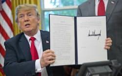 20日、米ワシントンのホワイトハウスで署名した大統領令を見せるトランプ大統領=AP