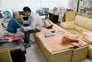 避難所で段ボールベッドに座って父親を介護する男性(21日、大阪府茨木市)