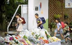 授業が再開し登校する児童。校門の献花台には多くの花が供えられていた(21日午前、大阪府高槻市立寿栄小)=共同