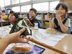 ガス供給停止で簡易給食のおにぎりなどを食べる小学生(21日、大阪府茨木市)