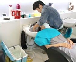 ガスの止まった美容室では、電気ポットでお湯を準備、クーラーボックスで温度を調整後にシャンプー(21日、大阪府高槻市)