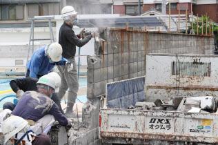 撤去作業が始まった中学校の塀(22日午前、大阪府池田市)