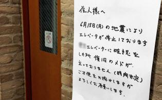 地震で停止したエレベーターの復旧の見通しが立たないことを知らせる張り紙(19日、大阪府吹田市、画像の一部を加工しています)=共同