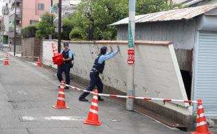 塀が電柱に倒れかかり、通行止めになった道路(18日午後、大阪府高槻市)