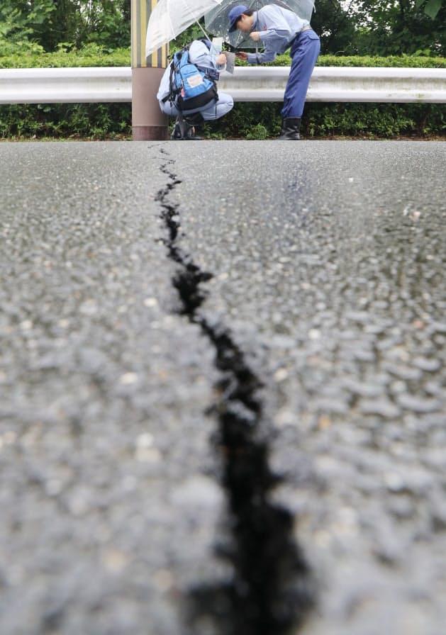 市街地の被害を調べる国土交通省の担当者(20日午後、大阪府高槻市)