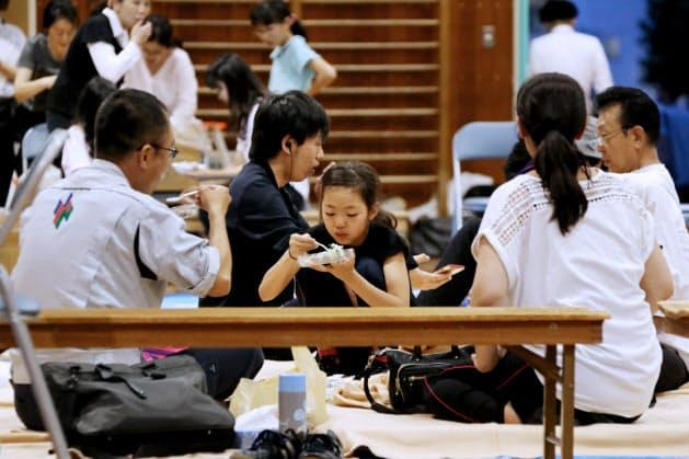 避難所になった小学校で配給された食事を取る被災者(18日午後、大阪府高槻市)