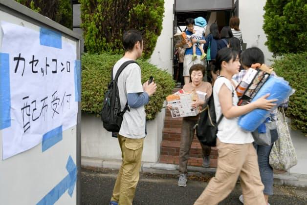 ブルーシートやカセットコンロを受け取る被災者(19日午後、大阪府高槻市)