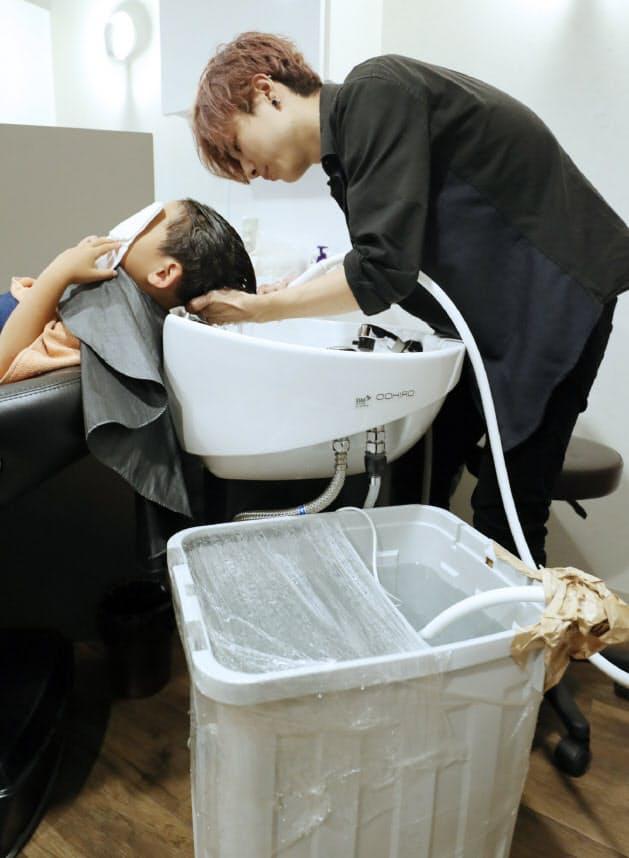 容器にためたお湯を使ったシャンプーの無料サービスを受ける男の子(22日午後、大阪府茨木市の美容室「トリコJR茨木店」)