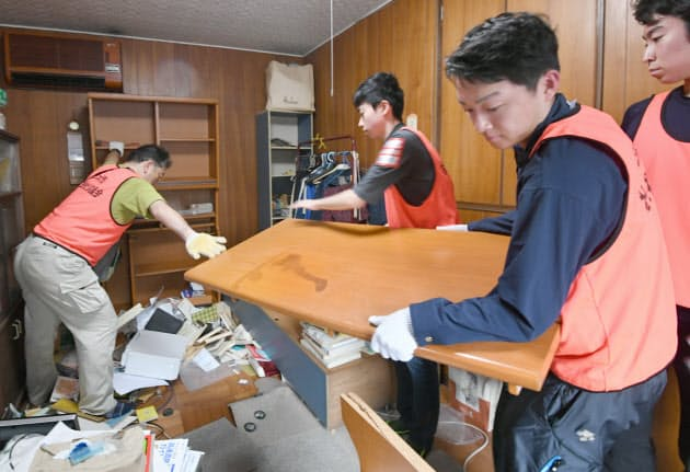ボランティア活動も本格的に動き出した。散乱した家具を運び出すボランティア参加者(23日午前、大阪府茨木市)