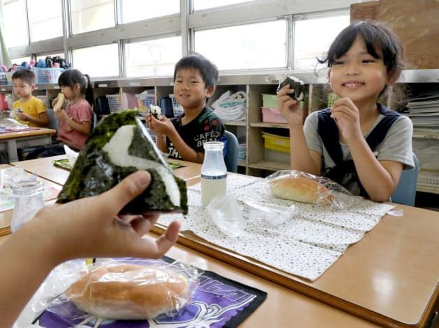 ガスの供給が止まり、簡易給食のおにぎりなどを食べる小学生(21日午後、大阪府茨木市の茨木小)