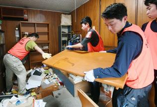 廃棄するため家財を運び出すボランティア(23日、大阪府茨木市)