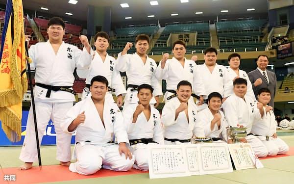 男子7人制で3連覇を果たし、ガッツポーズで記念写真に納まる東海大チーム(24日、日本武道館)=共同