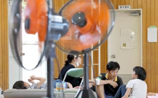 夏日となり扇風機が設置された避難所で過ごす被災者(24日、大阪府茨木市)