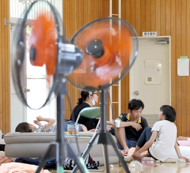 夏日となり扇風機が設置された避難所で過ごす被災者(24日午後、大阪府茨木市)