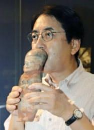 土偶の穴に息を吹き込む「BIZEN中南米美術館」の森下矢須之館長(岡山県備前市)=共同