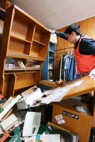 地震で倒れた棚を起こすボランティア(23日、大阪府茨木市)