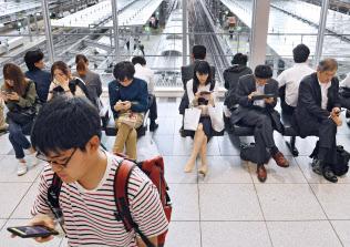 地震で電車が止まり、スマホを手に再開を待つ人たち(18日、JR大阪駅)