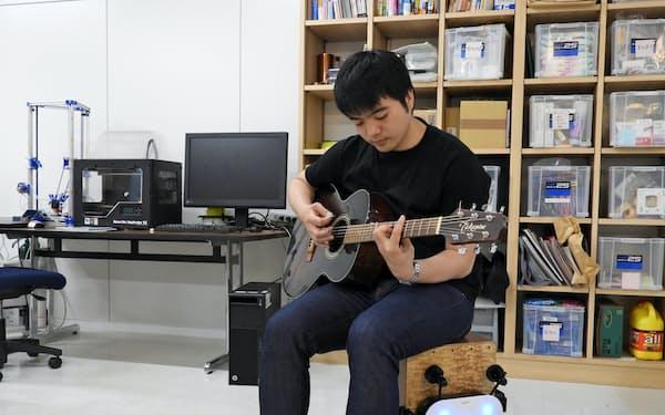 カホンの自動演奏に合わせてギターを奏でるUTSUWAの飯尾英晃社長