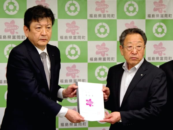 富岡町の宮本町長(右)から要請書を受け取る東電の小早川社長(28日午前、福島県富岡町)