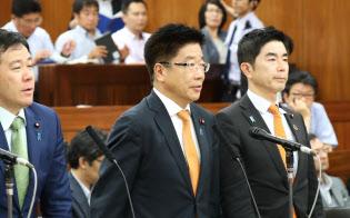 参院厚労委で働き方改革関連法案が可決され、一礼する加藤厚労相(中)(28日午後)