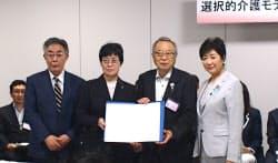 小池百合子知事(右)も混合介護のモデル事業の協定式に出席した(28日、東京都豊島区)