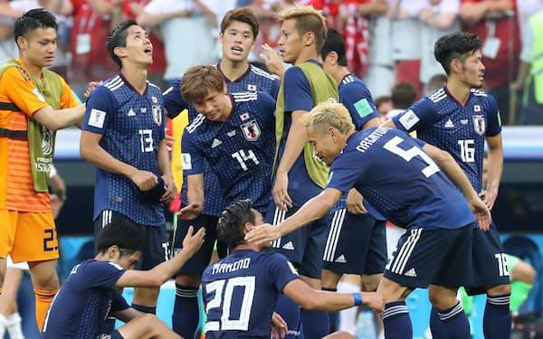 決勝トーナメント進出を決め、タッチを交わす日本イレブン=沢井慎也撮影