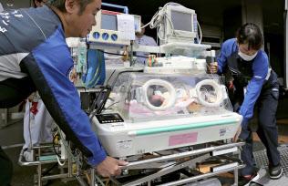 別の病院に搬送される乳児(18日、国立循環器病研究センター)=共同