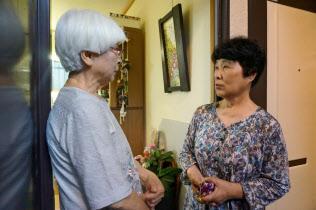 大阪府茨木市では民生委員(右)が日ごろから単身高齢者の見守りを行っている(29日、同市)
