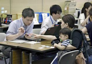 茨木市役所の罹災証明申請窓口で、スマートフォンで撮影された住宅の様子を確認する市職員(左端)=共同