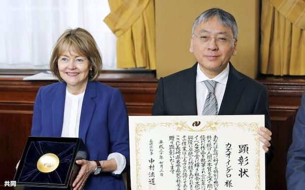 3日、ロンドンで長崎県の名誉県民称号を授与され賞状を手にするカズオ・イシグロさん。左は妻のローナさん=共同
