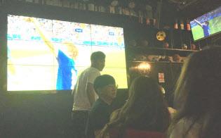 日本がゴールを決めるとスポーツバーに歓声が上がった(3日、北京)