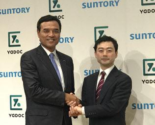 サントリーはオンライン診療システムを導入する(写真は、サントリーHDの新浪社長(左)とインテグリティ・ヘルスケアの武藤会長)