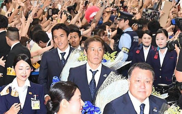 帰国し大勢の人たちに迎えられるサッカー日本代表の西野監督(中央)、長谷部選手(同左)ら(5日午前、成田空港)