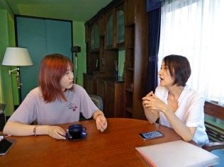 シェア経済の象徴として期待された民泊だが、課題は多い。写真は家主と話す中国人観光客(左)