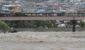 大雨で増水した安威川。奧には大阪北部地震の影響でブルーシートがかけられた家屋の屋根が見える(5日午後、大阪府茨木市)