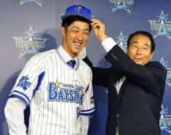 DeNAの入団会見で高田繁GM(右)から帽子をかぶせてもらう中後(5日、横浜市内の球団事務所)=共同