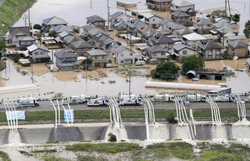 建物が水没、浸水した岡山県倉敷市真備町地区で始まった排水作業(8日午後2時43分)=共同