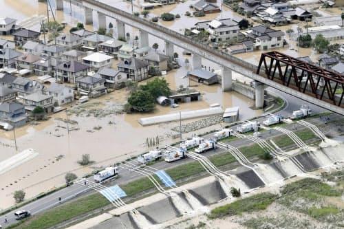 建物が水没、浸水した岡山県倉敷市真備町地区で始まった排水作業(8日午後2時46分)=共同