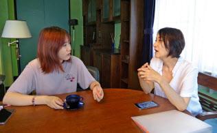 東京都渋谷区では条件を満たせば制限地域で規制を緩める(家主と談笑する中国人観光客(左))