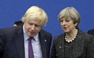 英国のメイ首相(中央)と話すジョンソン氏(左)=5月、ブリュッセル(AP)