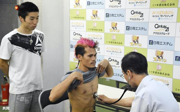 WBOミニマム級タイトルマッチの予備検診を受けるビック・サルダール。左は山中竜也(10日、神戸市)=共同