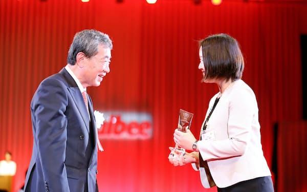 カルビーは社内表彰者に自社株を付与している(6月、社員を表彰する松本晃会長=当時(左))